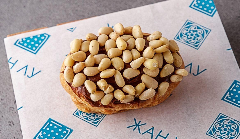 Эклер с сырной начинкой, шоколадным топингом и кедровым орехом